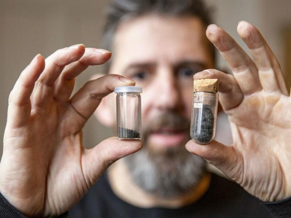 Le chercheur tient deux petites bouteilles qui contiennent des roches.