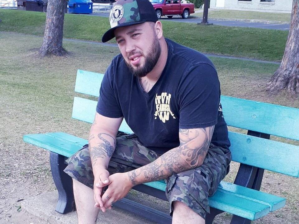 L'homme est assis sur un banc.  Photographie tirée de sa page Facebook