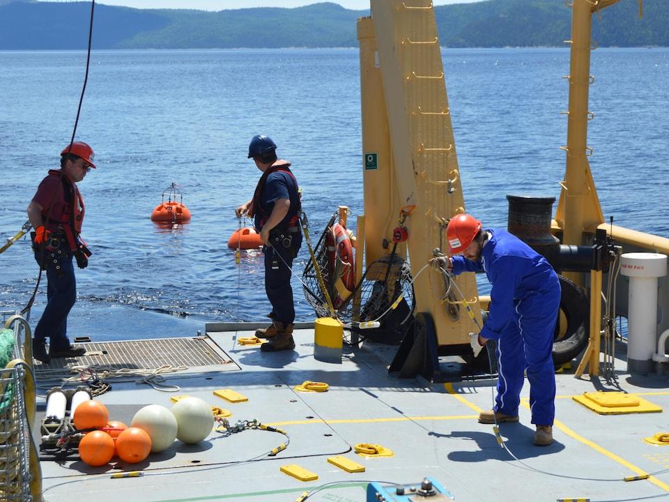 On voit trois personnes s'affairer sur le pont d'un navire. Ils mettent à l'eau l'instrument de mesure, muni de grosses bouées. En arrière-plan on voit le fjord du Saguenay.