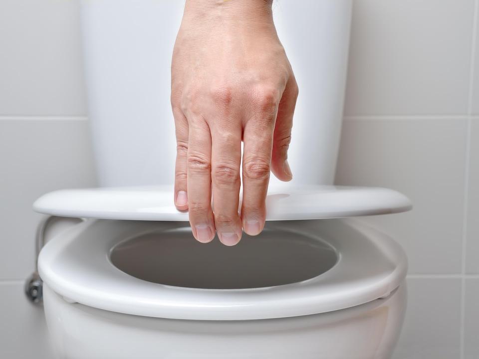 Une main ferme le couvercle d'une toilette publique.
