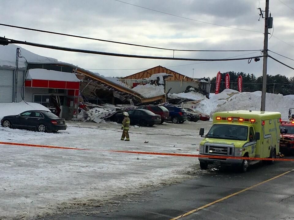 Derrière un périmètre de sécurité, une partie du toit d'un bâtiment est affaissée sur des véhicules stationnés. Une ambulance est sur les lieux.