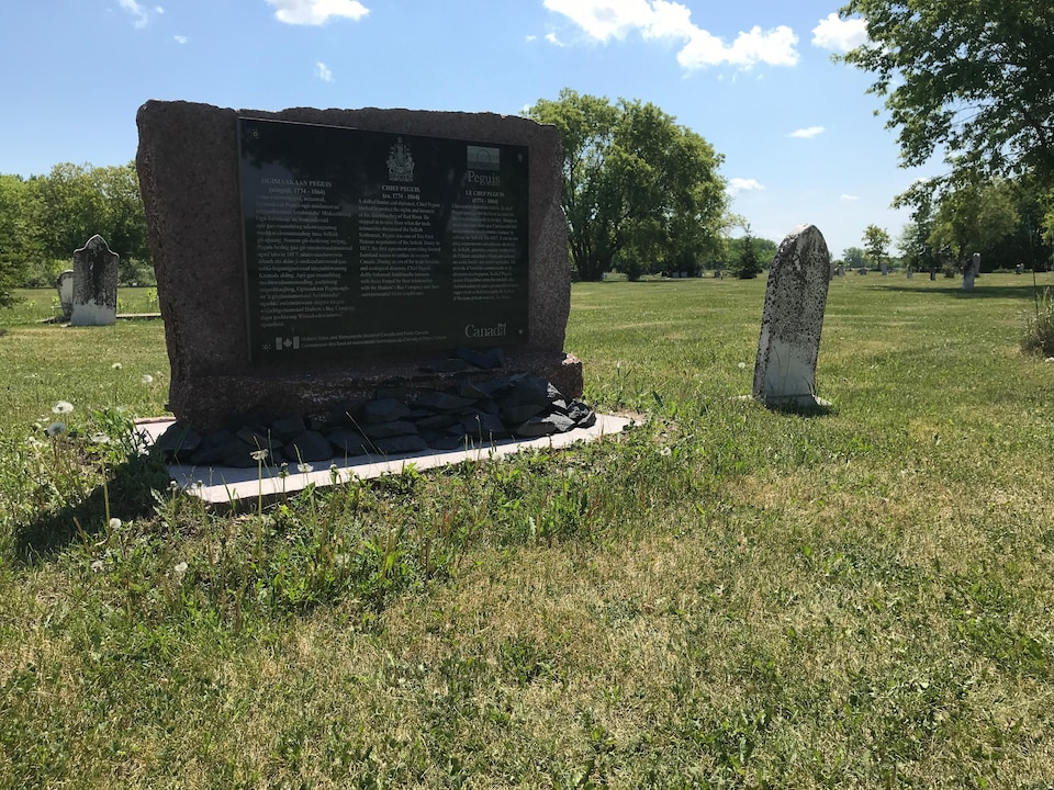 Une petite pierre tombale blanche accompagnée d'un grand panneau explicatif sur qui était le chef autochtone Peguis.