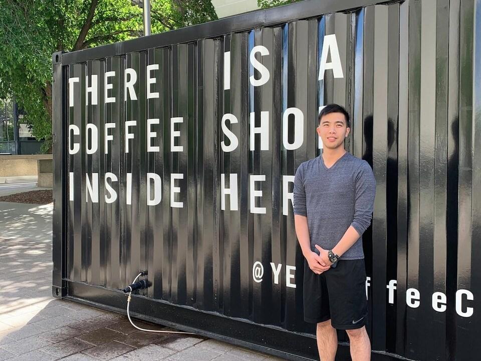 Tony Phung pose devant son café mobile. L'inscription « There is a coffee shop inside here » est écrite en majuscule sur une des façades du conteneur.