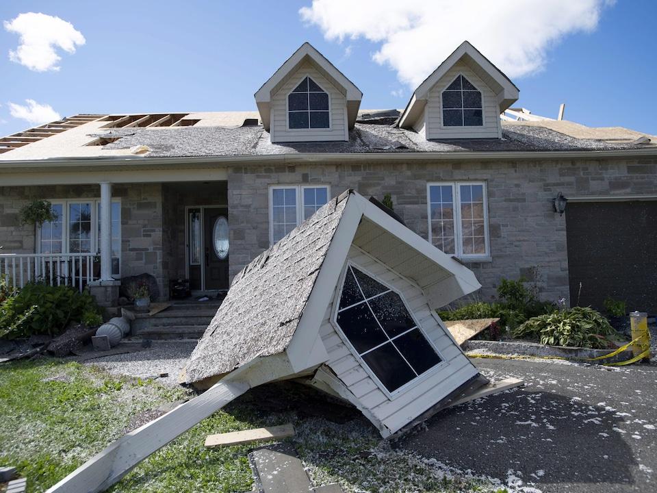 Une partie du toit d'une maison a été arraché par la force des vents et se trouve maintenant au sol, dans l'entrée de la demeure.