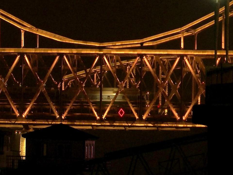 Un train voyage rapidement sur un pont illuminé en pleine nuit.