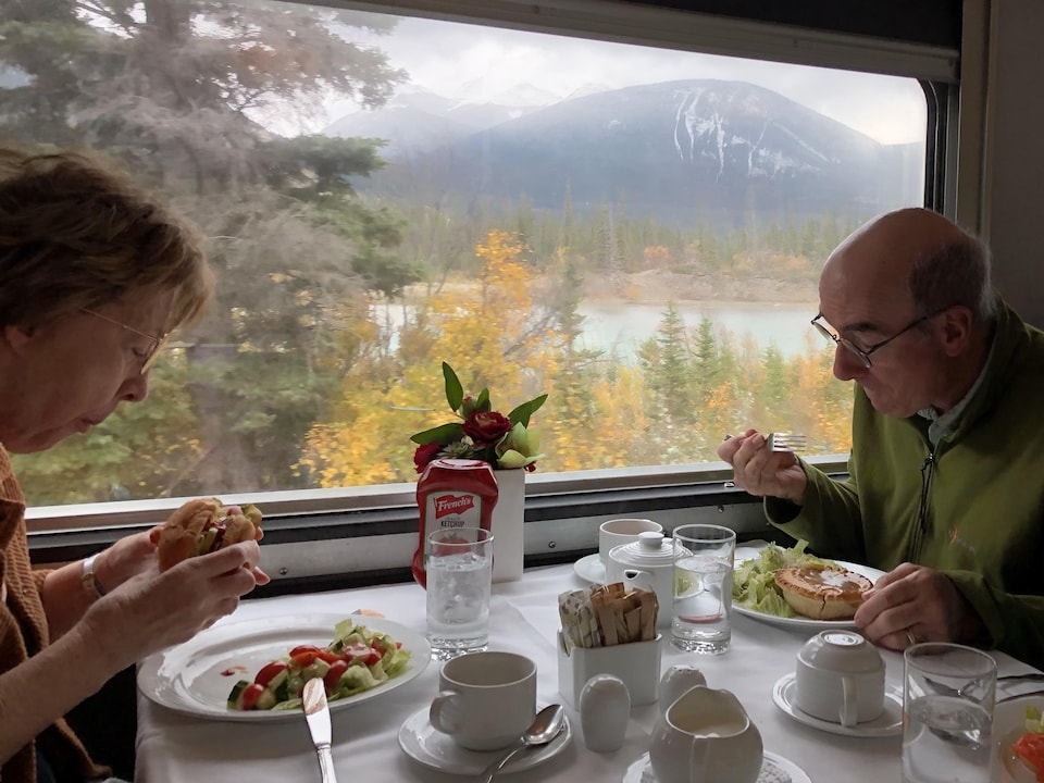 Un couple assis à une table devant une fenêtre donnant sur un paysage des Rocheuses.