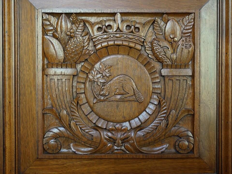 Un castor, des feuilles d'érable et une couronne sont sculptés dans le trône en bois.