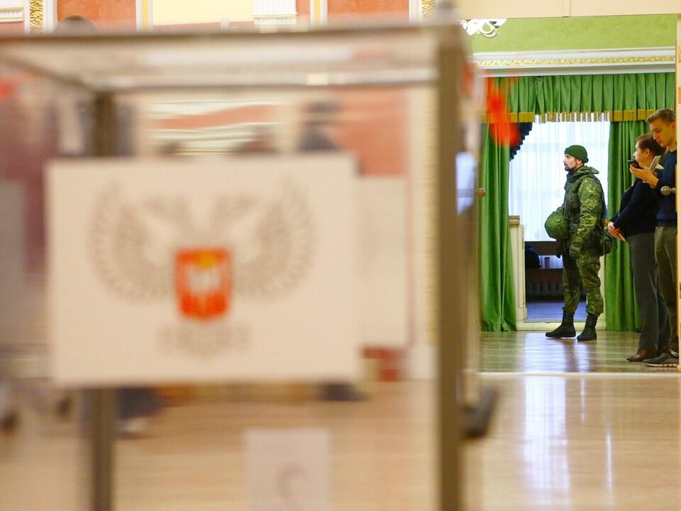 Un homme en uniforme de combat surveille l'entrée d'un bureau de vote dans l'est de l'Ukraine.