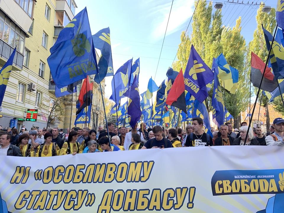 Des manifestants munis de drapeaux tiennent une banderole comportant une inscription en cyrillique.