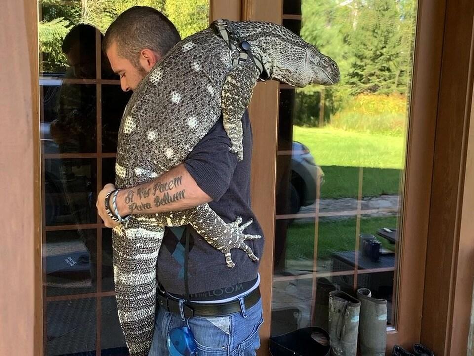 Olivier Frigon tient son reptile avec son bras gauche et ouvre une porte avec son bras droit.