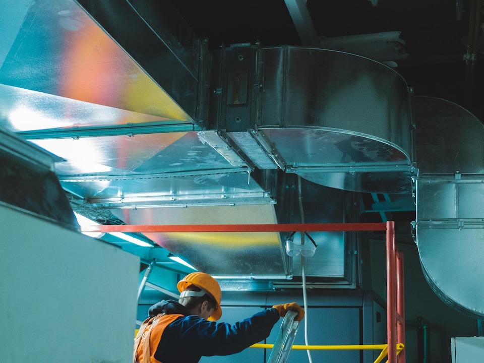 Un homme met en place un système de ventilation mécanique.