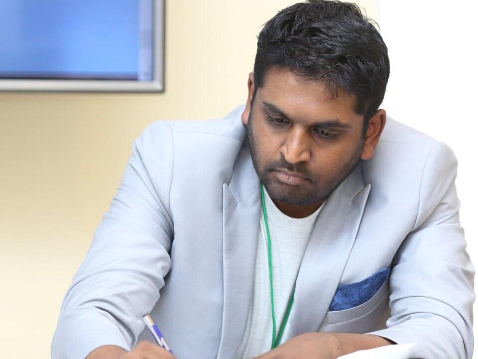 Vijay Stelur dans un bureau en train d'écrire.