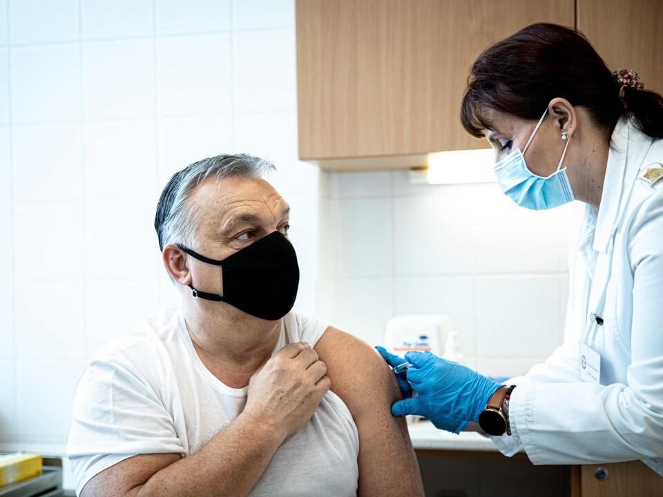 Un homme masqué se fait injecter le vaccin dans le bras.