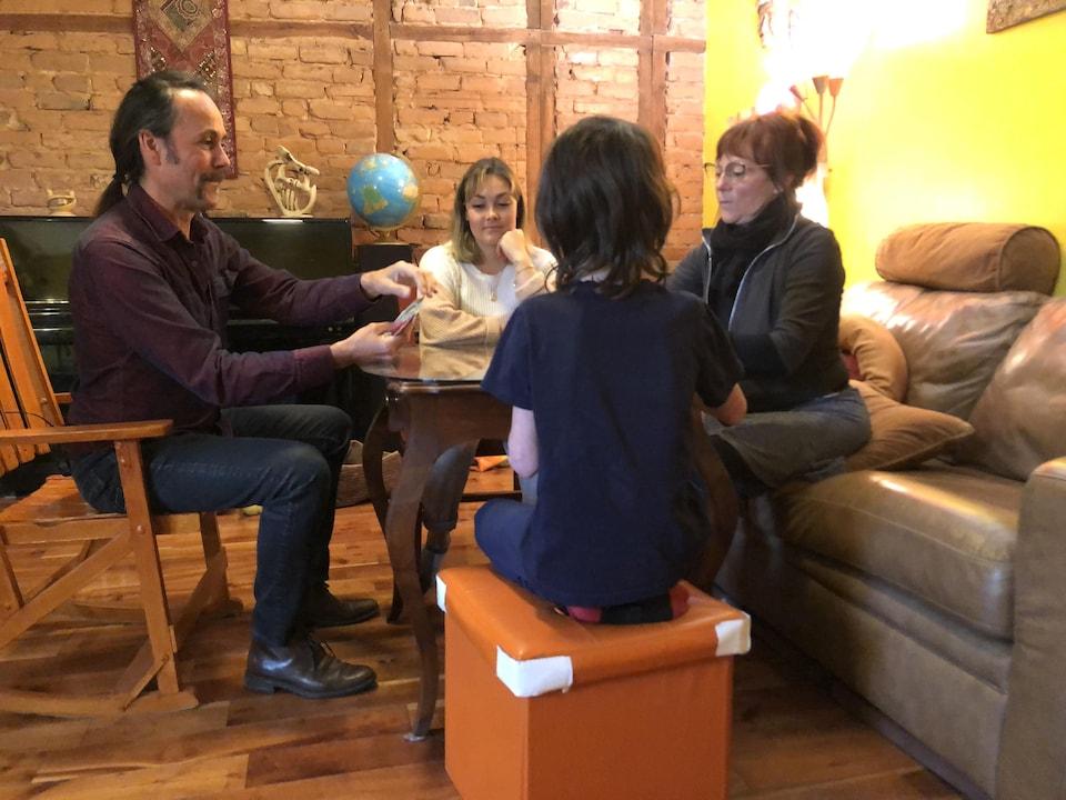On voit la famille de quatre assis à une table dans une demeure. Ils jouent aux cartes.