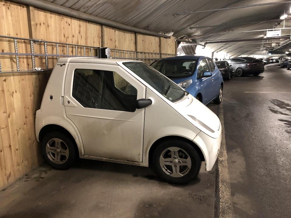 Une toute petite voiture prend une fraction de l'espace de stationnement d'une voiture régulière.