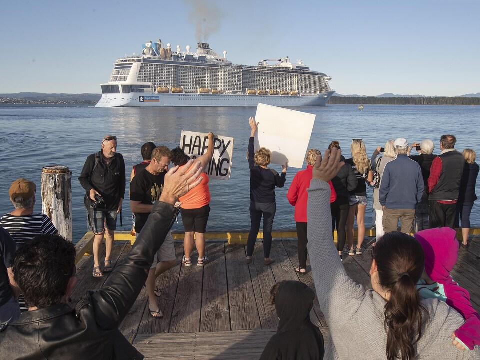 Plusieurs personnes se tiennent sur un quai, le bateau voguant en arrière-plan.