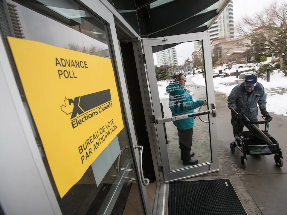 Un électeur entre dans un bureau de vote avec une marchette sur roue.