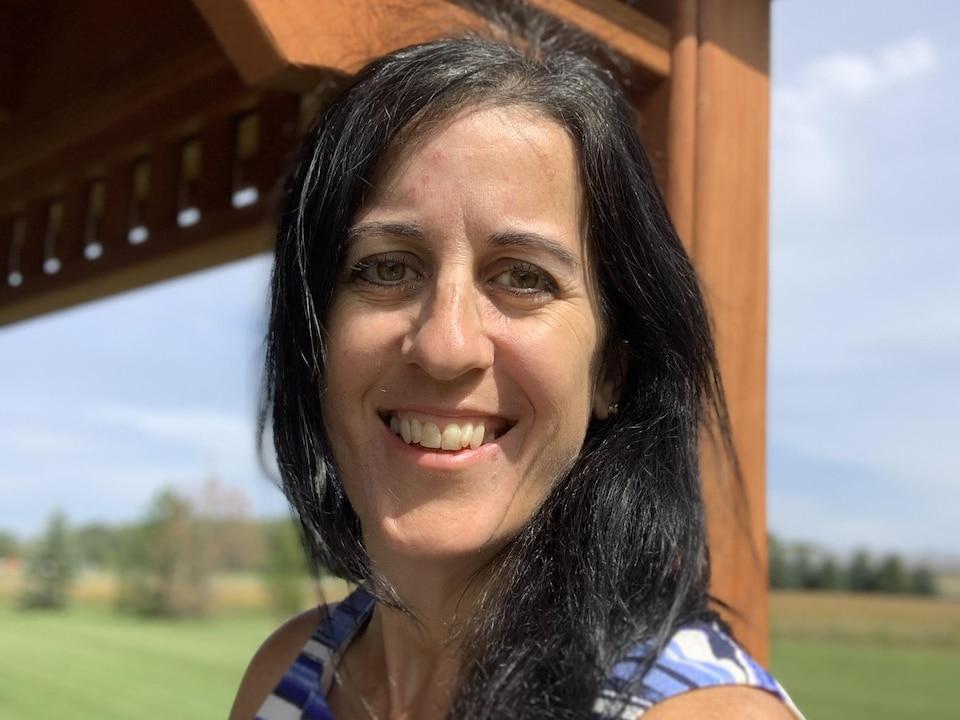 Une femme aux cheveux longs et noirs, souriante. La photo a été prise dehors.