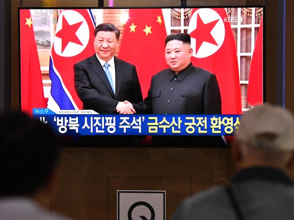 Deux personnes à l'avant-plan regardent un écran de télévision sur lequel on voit Xi Jinping et Kim Jong-un se serrer la main lors d'une rencontre diffusée à la télévision coréenne CCTV.