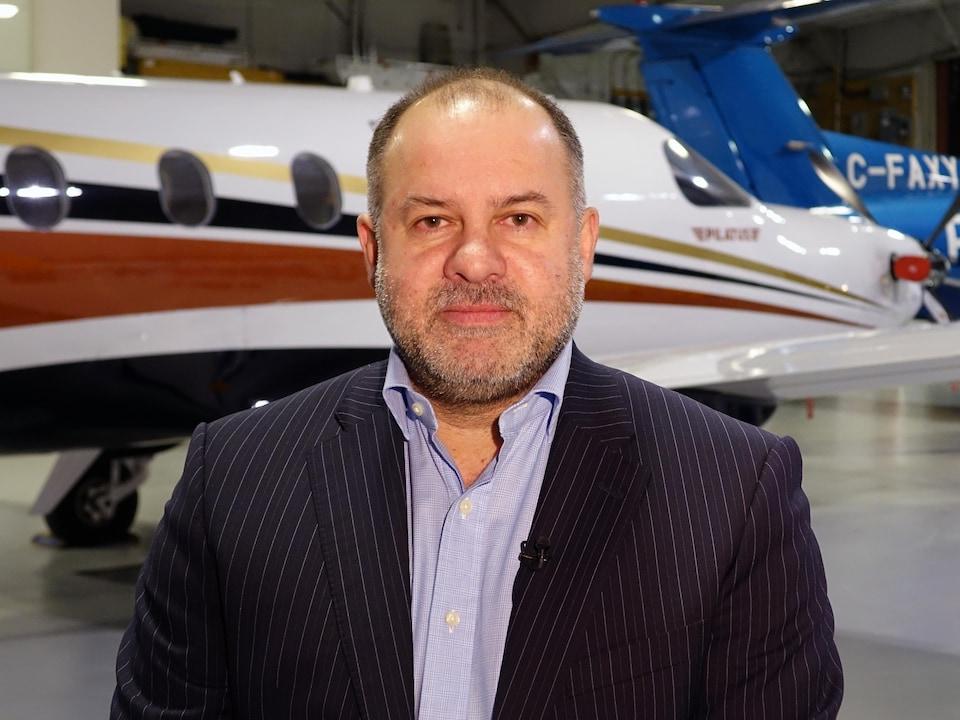 Yani Gagnon dans un hangar avec des avions de sa compagnie.