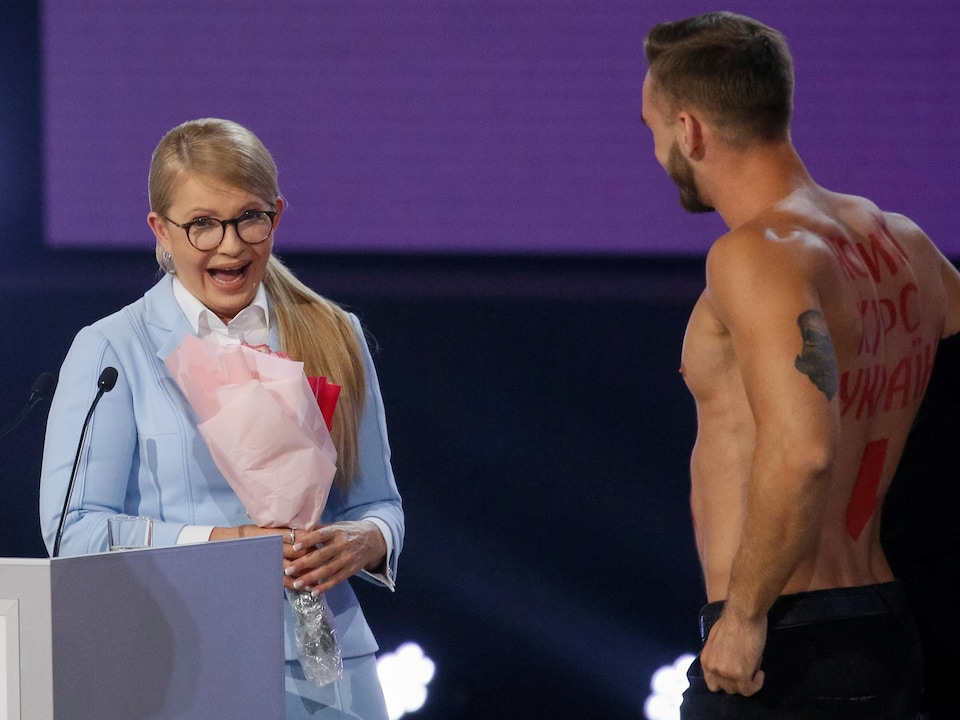 Un homme est torse nu, des inscriptions en cyrilliques sont visibles sur son dos. Ioulia tient un bouquet de fleur et semble surprise.