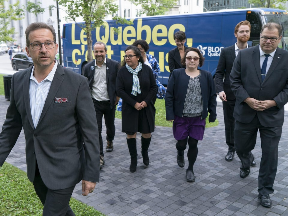 Yves-François Blanchet marche tout près de son autobus de campagne. Il est suivi par plusieurs personnes.