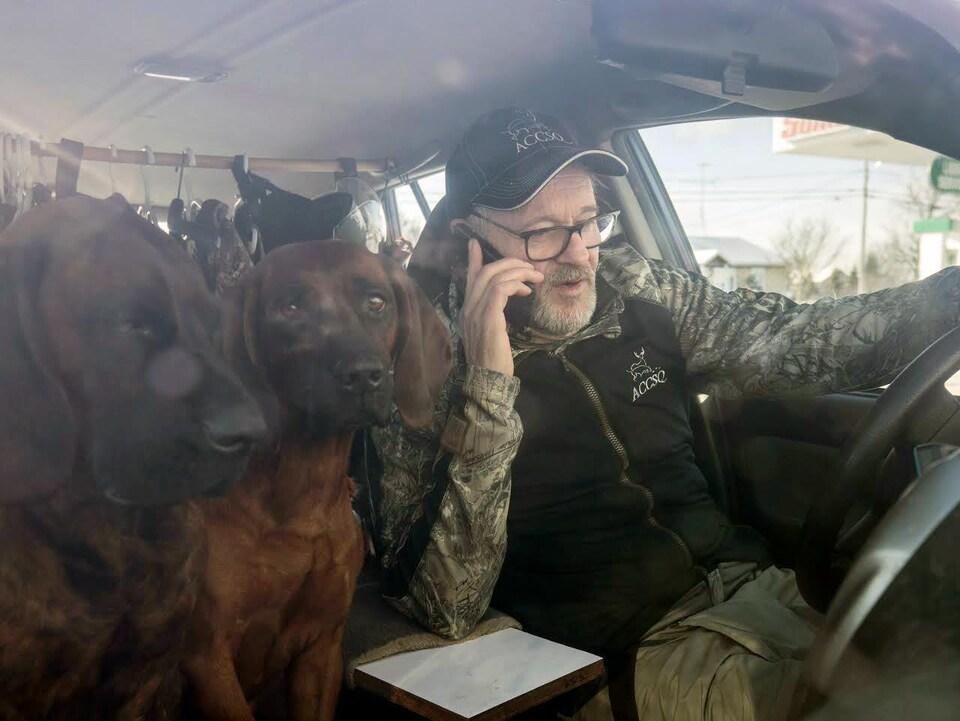 On voit M. Martineau au volant de son véhicule stationné. Il parle au téléphone. À côté de lui se trouvent deux chiens.