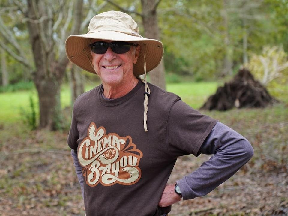 Un homme portant un chapeau et des lunettes fumées devant un arbre déraciné.