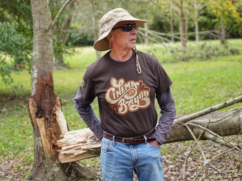 Un homme portant un chapeau devant un arbre au tronc cassé.