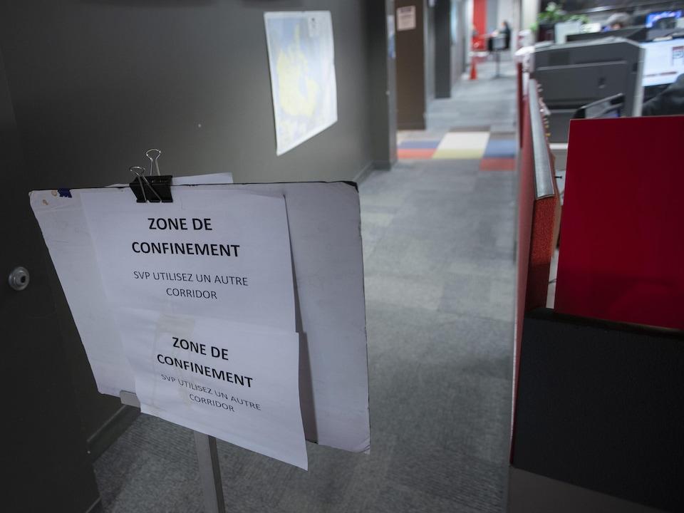 Sur une affiche, il est écrit : Zone de confinement. SVP, utilisez un autre corridor.