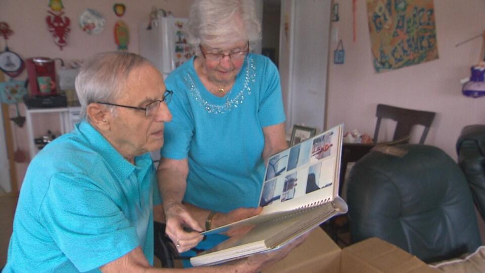 Homme et femme âgés regardent un album photo.