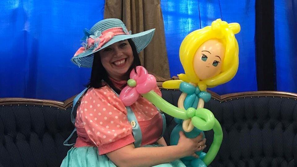 Isabelle cliche est assit en costume avec une poupée fait entièrement avec des ballons