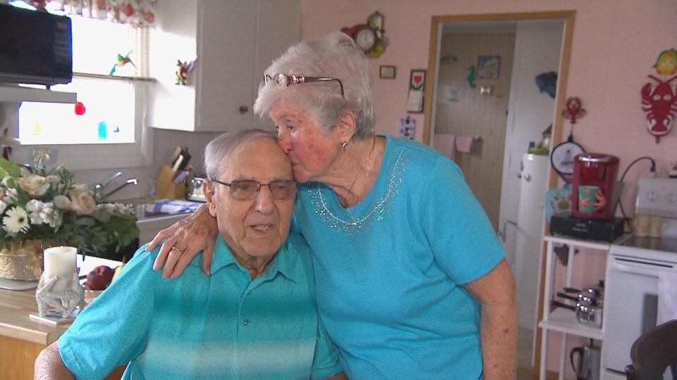 Une femme âgée embrasse un homme sur le front.