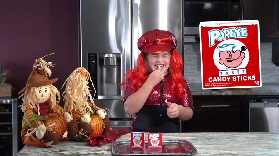 Une fillette grimace en croquant un bâtonnet de bonbon.