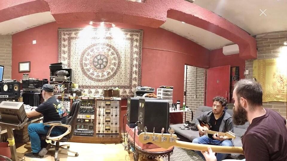 Trois hommes dans un studio de musique. Deux musiciens et un producteur en préparation du prochain album de Cristian de La Luna.