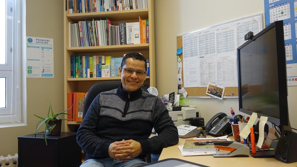 Un homme pose dans son bureau avec un visage souriant.