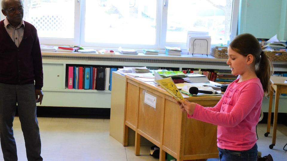 Une jeune fille lit un texte debout devant la classe.