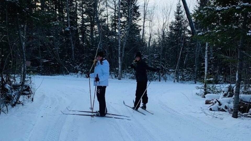 La mère et sa fille sont debout avec leurs skis parmi les conifères.