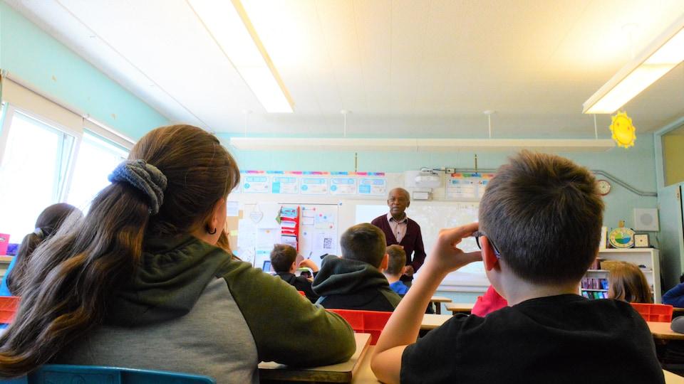 Un homme raconte une histoire à des enfants captivés.