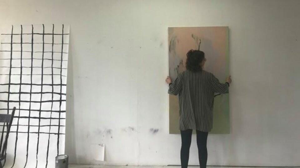 L'artiste en art visuel Laurence Belzile en train de placer une peinture dans son atelier de Québec