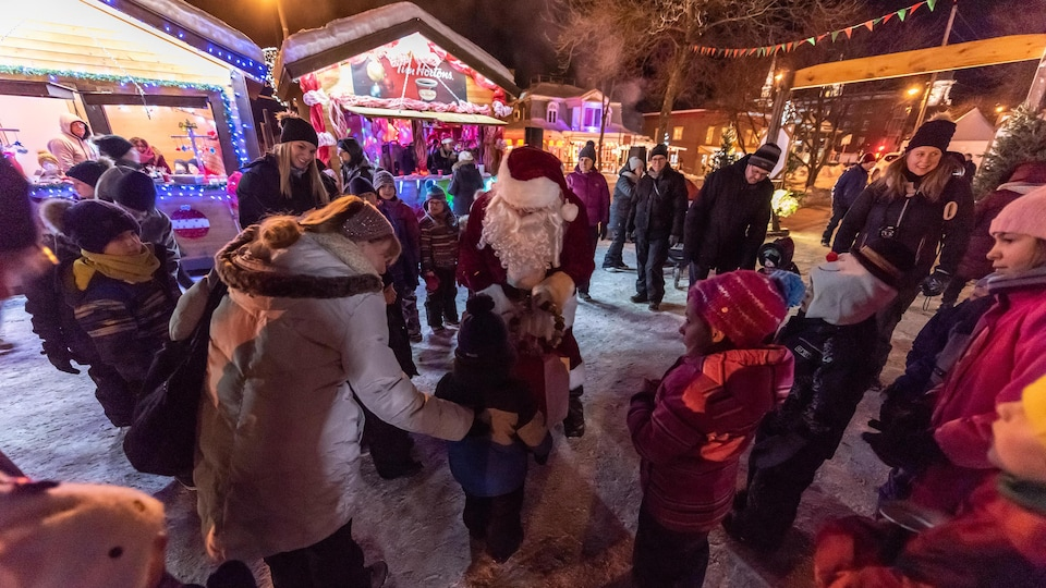 Le père Noël s'adresse à des enfants entouré de petites cabanes décorées de guirlandes.