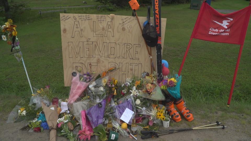 Des bouquets de fleurs, une paire de bottes de ski et des pôles jonchent une pancarte sur laquelle est écrit : «À la mémoire de Phil».
