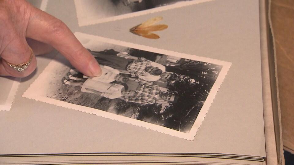 Photo ancienne, un doigt montre une jeune fille  au centre d'une famille.