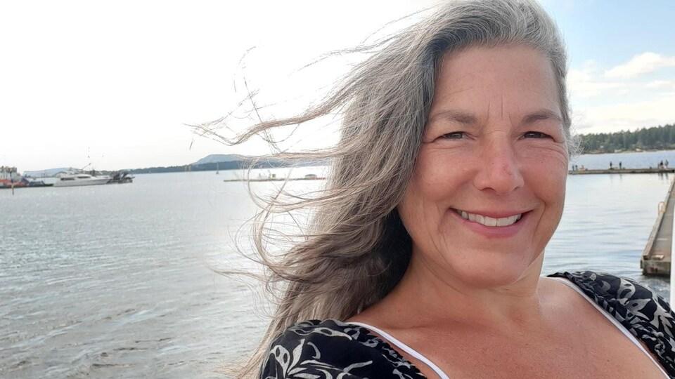 Une femme sourit à la caméra. Elle est sur le quai et on peut voir l'océan derriere elle.