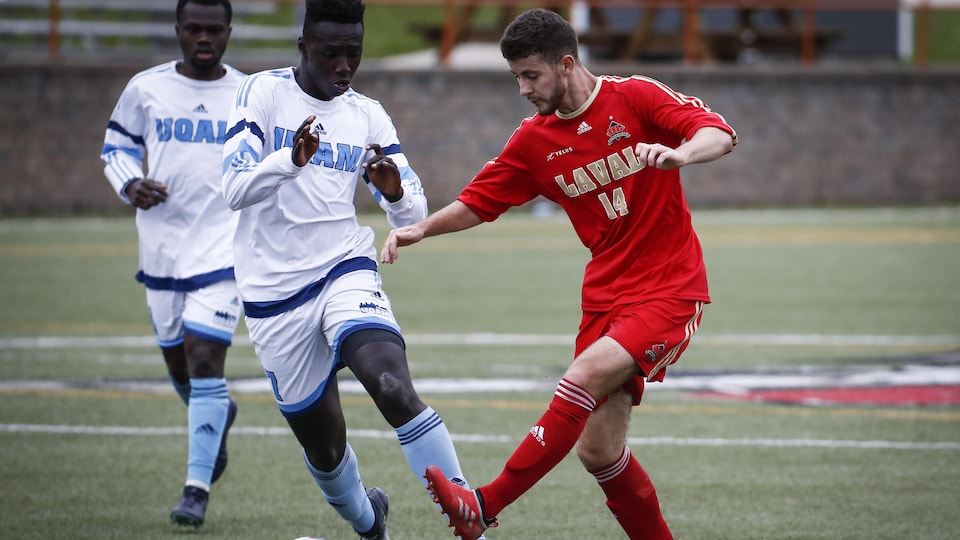 Un joueur de soccer vêtu de rouge contrôle ballon devant deux adversaires vêtus de blanc.