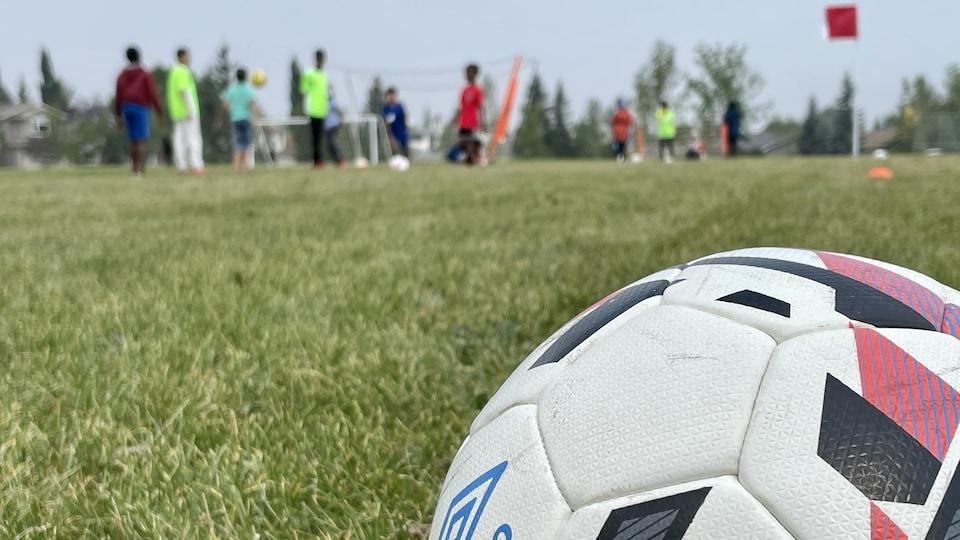 Un ballon de soccer avec en arrière-plan des enfants qui jouent.