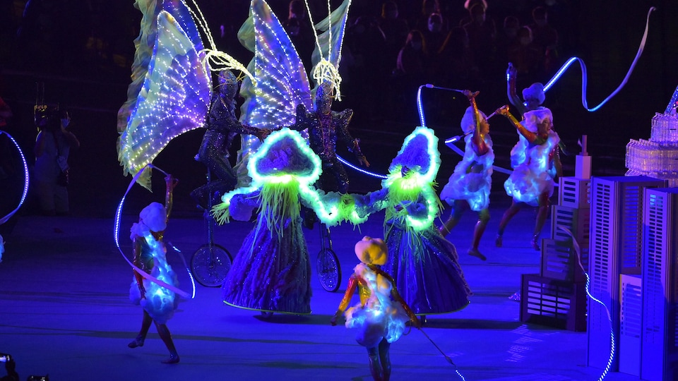 Artists dance with glowing costumes.