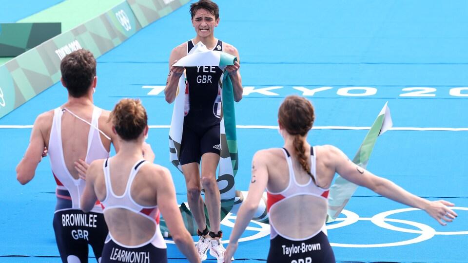 Un triathlète termine sa course et se dirige vers ses coéquipiers qui l'attendent les bras ouverts après une victoire.