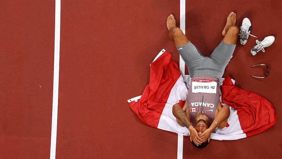 Andre De Grasse couché sur le drapeau canadien.