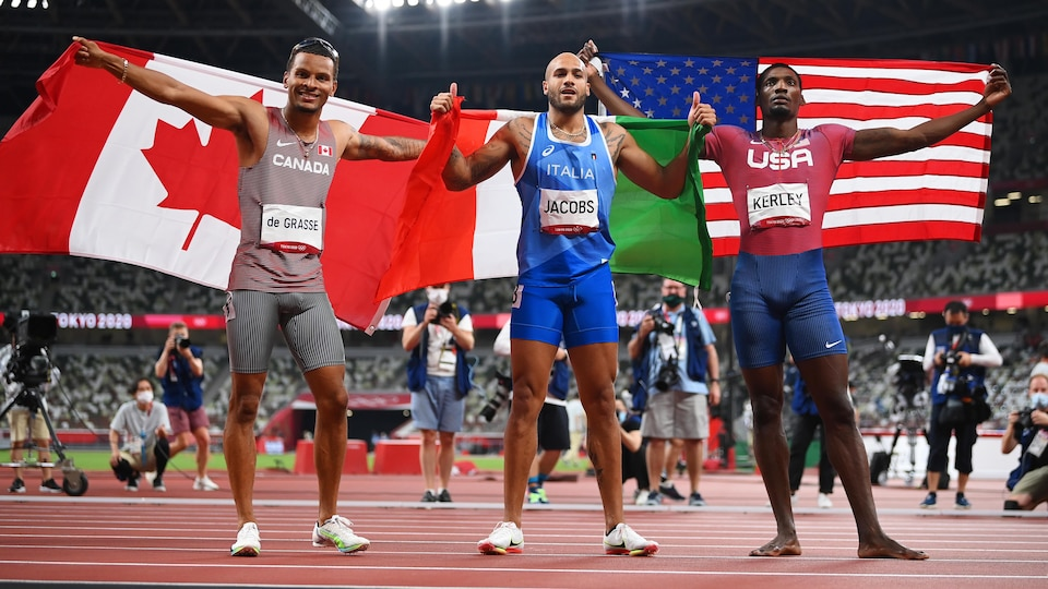 Ils célèbrent leurs médailles en tenant le drapeau de leur pays par-dessus les épaules.